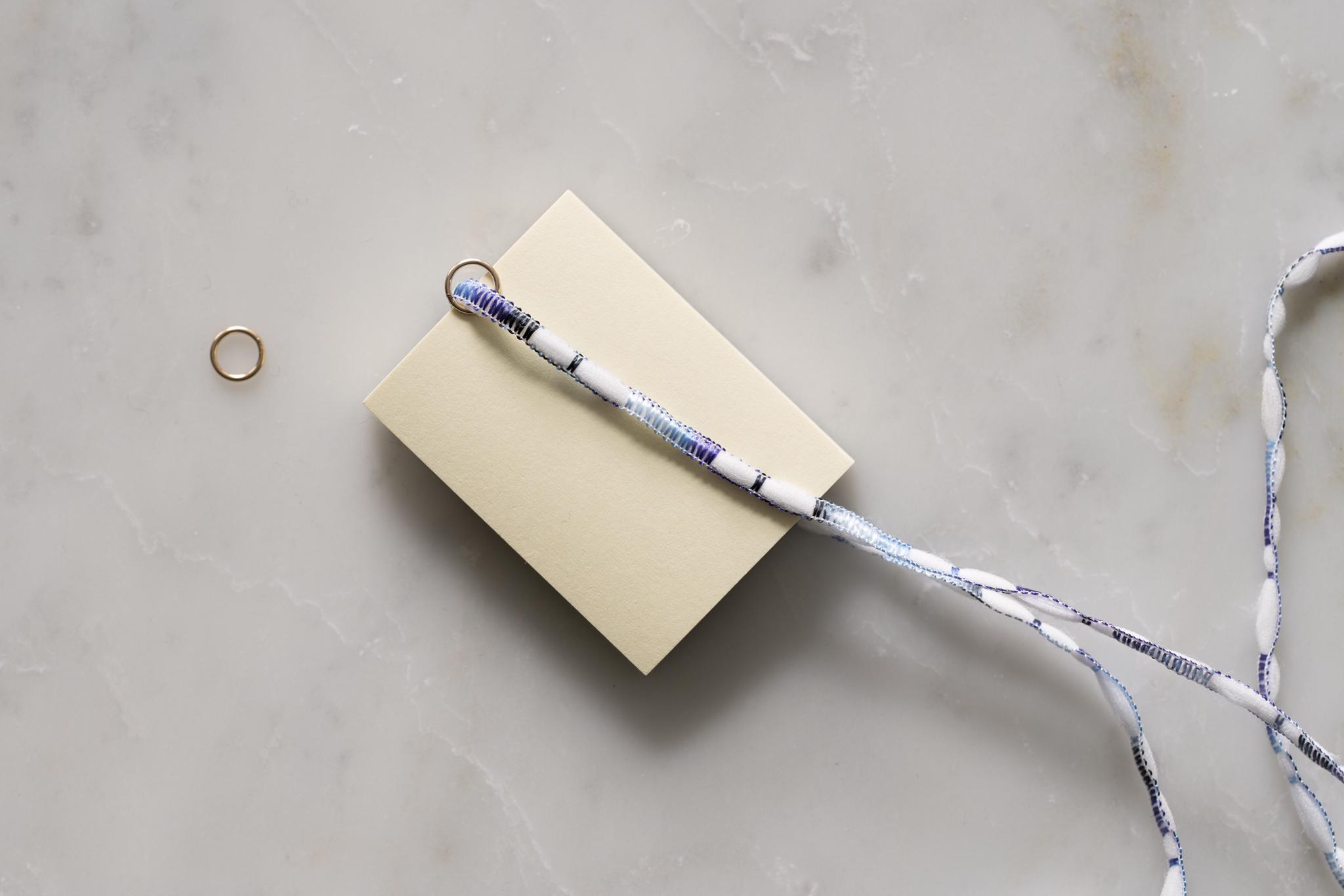 タッセルフリンジの作り方(2)-紐の半分の長さのところに丸カンを移動させて、台紙に紐を巻いていきます