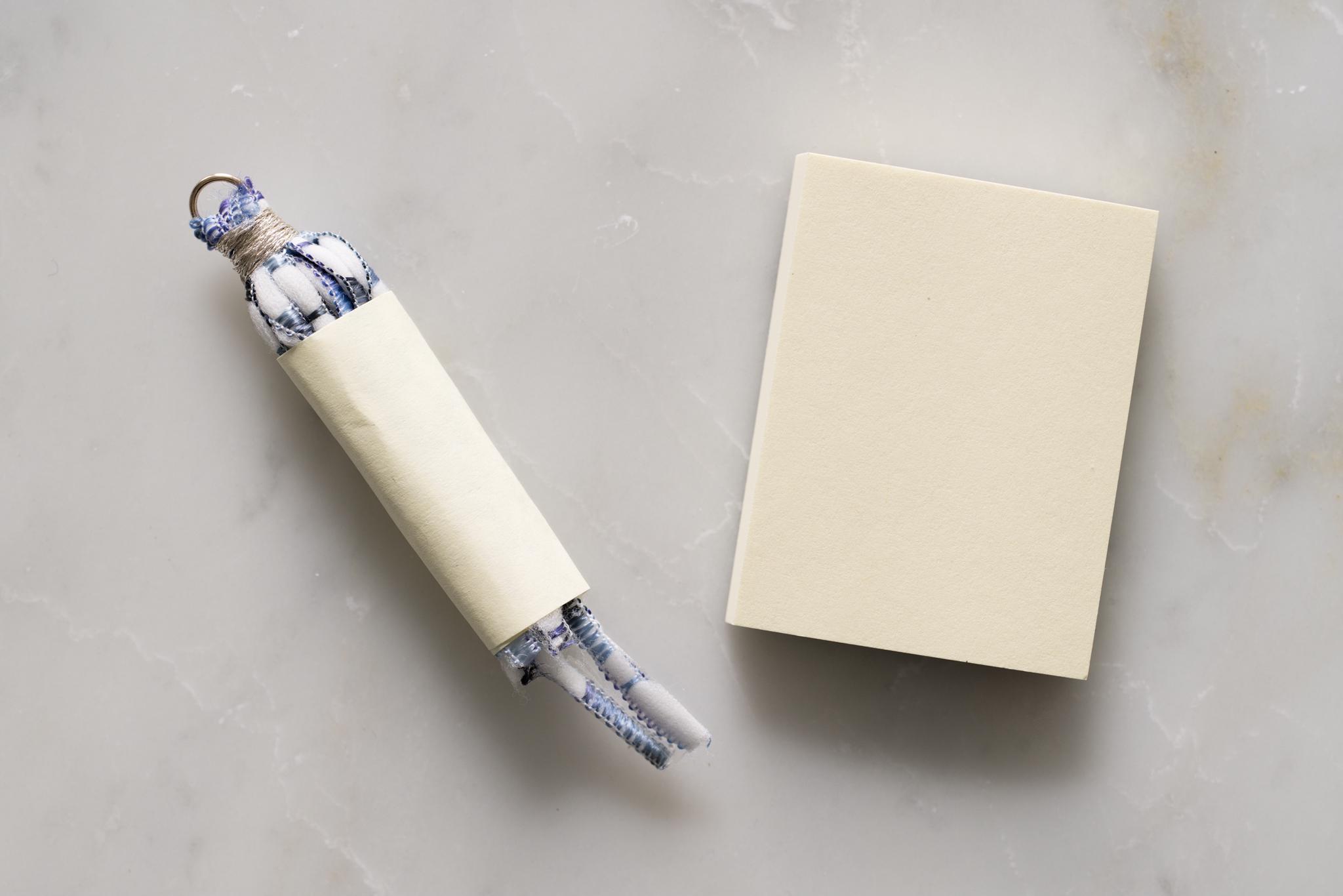 タッセルフリンジの作り方(7)-紐の端が少し出るよう紙を巻いてテープで留めます